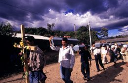 EL SALVADOR. El Mozote. 2001. Family members carry the coffins with exhumed remains through the plaza of El Mozote.